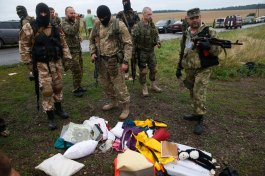 Pro-Russian separatists look at passengers' belongings at the crash site of Malaysia Airlines flight MH17, near the settlement of Grabovo in the Donetsk region